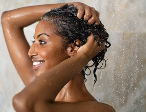 Como deixar o cabelo mais brilhoso: mulher lava o cabelo durante o banho.