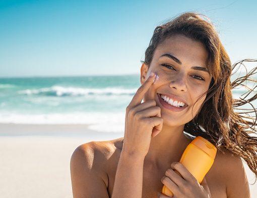 Usar protetor solar diariamente: mulher utiliza o produto no rosto.