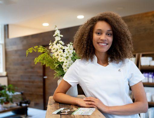 Como abrir uma clínica de estética: mulher sorrindo no trabalho.