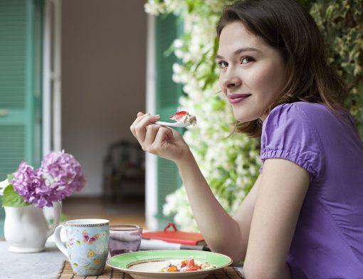 Como iniciar uma rotina saudável: mulher comendo frutas.
