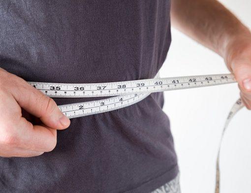 Perder gordura abdominal: homem com fita métrica em volta da cintura.